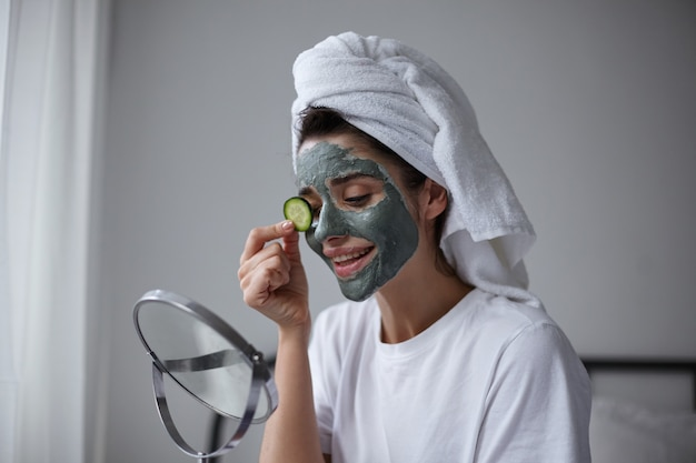 Close-up of pretty young brunette woman with towel on her head putting fresh cucumber on her eye while doing beauty treatment in early morning, sitting over home interior Free Photo