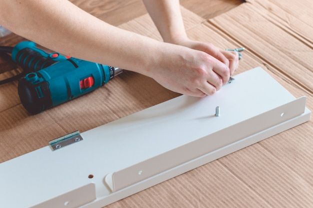 Close-up of the process of installation a furniture  with electric screwdriver Premium Photo