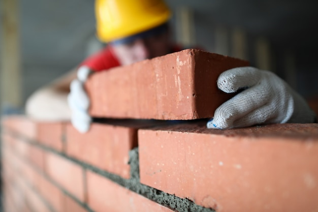 Close-up of professional construction worker laying bricks in industrial site. builder in protective uniform. man building wall with blocks. renovation concept Premium Photo