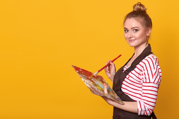 Close up profile portrait of happy female artist, holding palette and paintbrush in hands, standing against yellow Free Photo