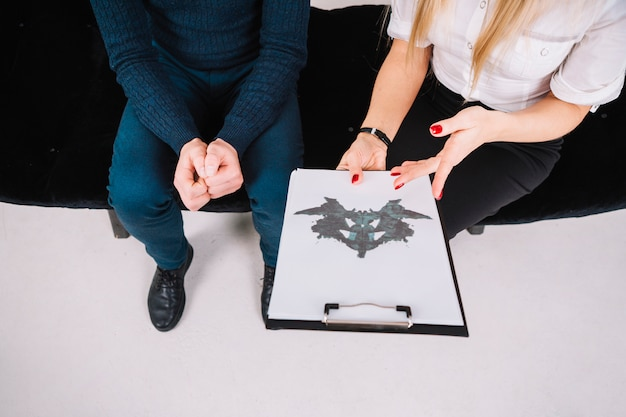 Close-up of a psychologist showing rorschach inkblot on clipboard to patient Free Photo