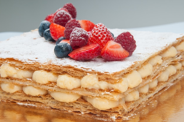 Close-up of puff pastry layer cake decorated with fresh berries Free Photo