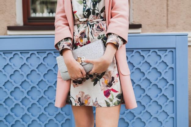 ピンクのコートで街を歩いて魅力的なスタイリッシュな女性の財布を閉じる 無料写真