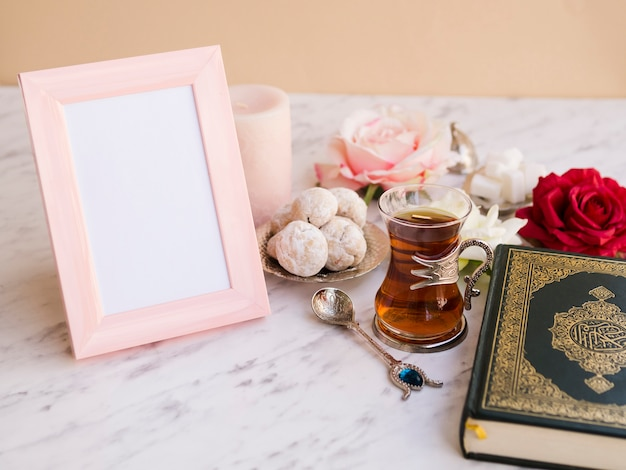Close up quran on festive table with picture frame Free Photo
