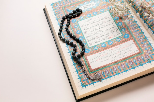 Close up quran and prayer beads arrangement Free Photo