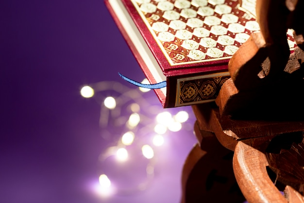 Close up quran wih defocused string lights Free Photo