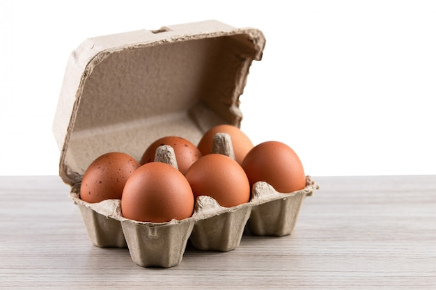 Close up of raw chicken eggs in egg box, organic food from natural on rustic wood table Premium Photo