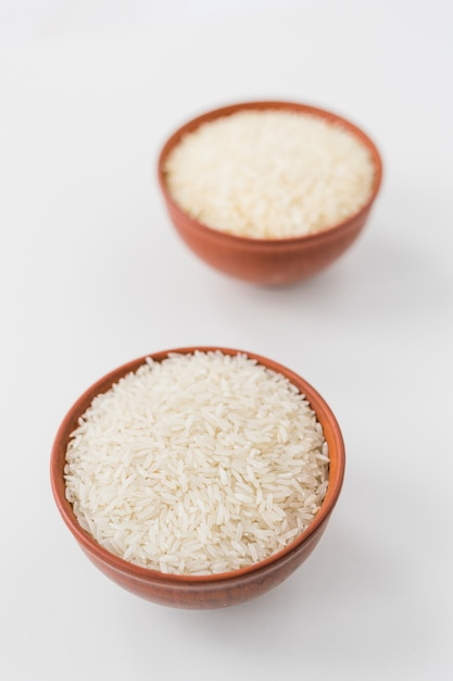 Close-up of raw jasmine rice bowls on white wallpaper Free Photo