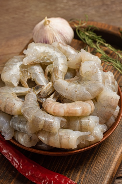 Close up of raw shrimps on wooden background. Free Photo