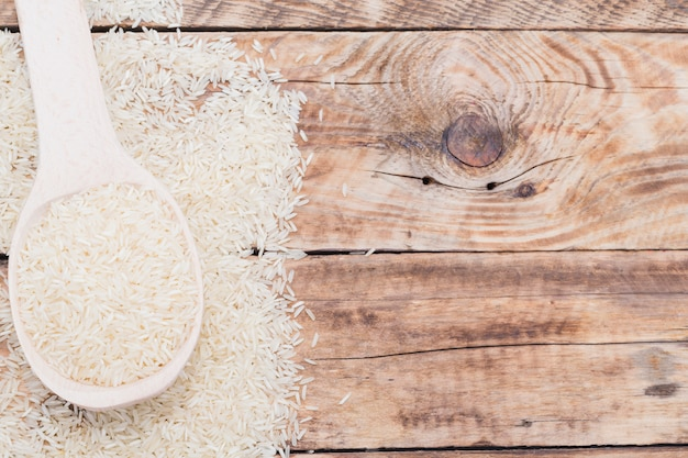 Close-up of raw white rice in spoon over textured plank Free Photo