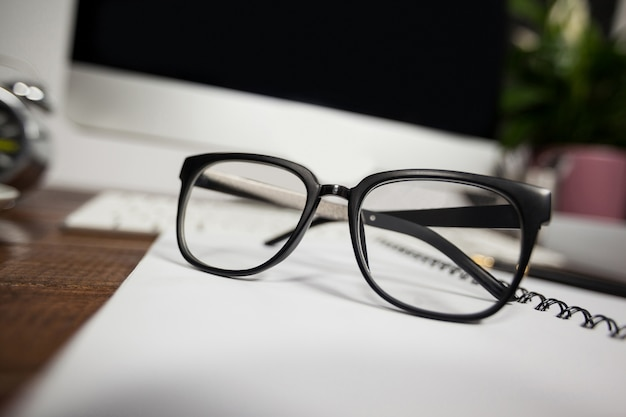 Close- up of reading glasses on office desk Free Photo