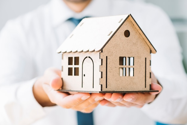 Close-up real estate agent with toy house Free Photo