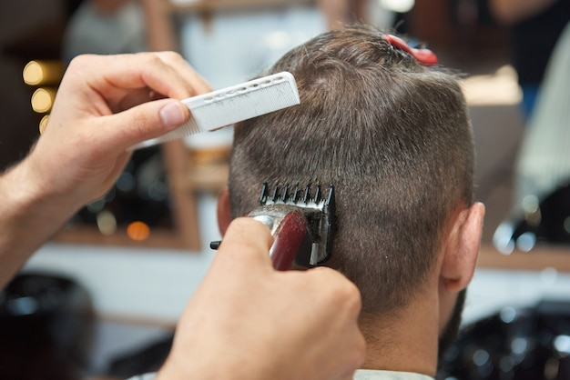 Close up rearview of a man getting a new hairstyle by professional barber Premium Photo