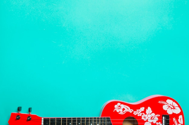 Close-up of red acoustic classic guitar on turquoise background Free Photo