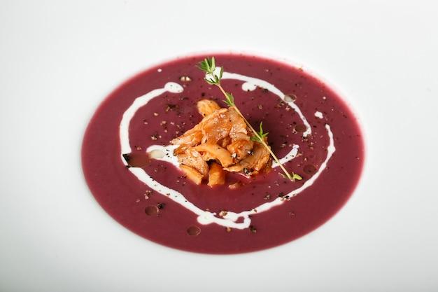 Close up of red cream soup with squid dish Premium Photo