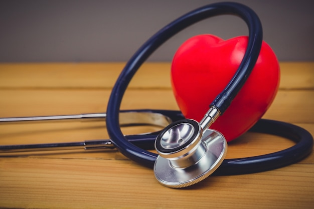 Close up red heart and stethoscope on old wood table Premium Photo