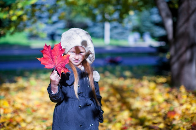 Close-up red maple leaf in the hands of little girl on beautiful fall day Premium Photo