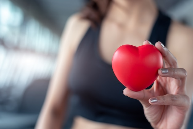 Close up of red massage ball like heart shape in fitness woman hand at sport gym Premium Photo
