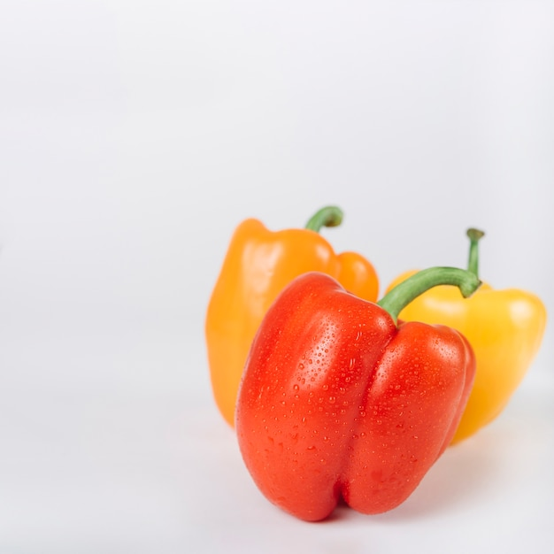Close-up of red; orange and yellow bell peppers on white backdrop Free Photo