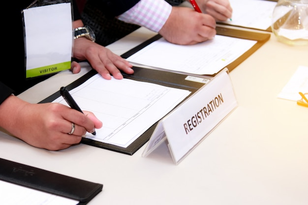 Close-up of registration desk in front of conference center with businessman Premium Photo