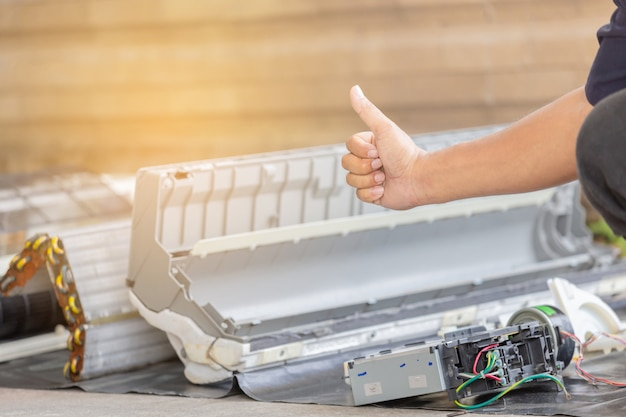 Close up of repairman giving thumb up after cleaning air conditioner compartment Premium Photo