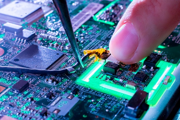 Close up repairmans finger on the green electric circuit board Premium Photo