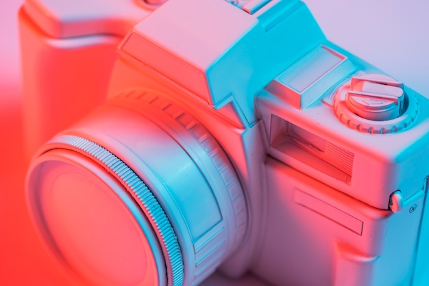 Close-up of retro pink camera with blue light Free Photo