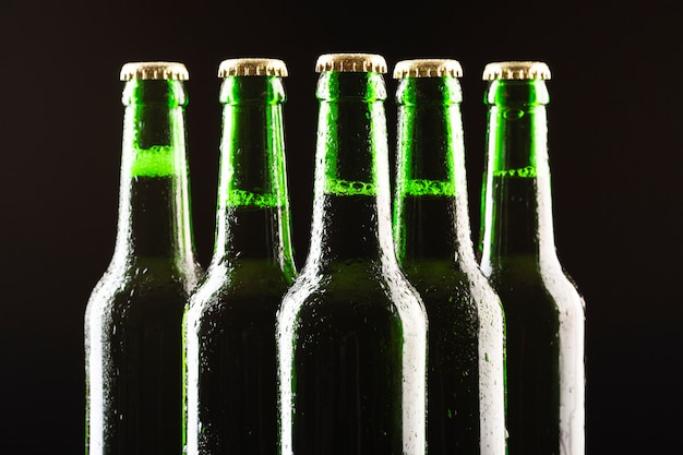 Close-up row of beer bottles Free Photo