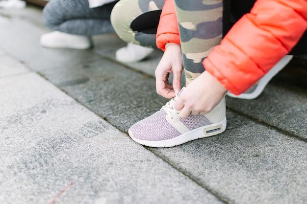 Close-up of runner tying shoelace Free Photo