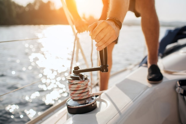 Close up of sailor winds around rope by using handle for coiling. he works with both hands. young man stands on yacht. Premium Photo