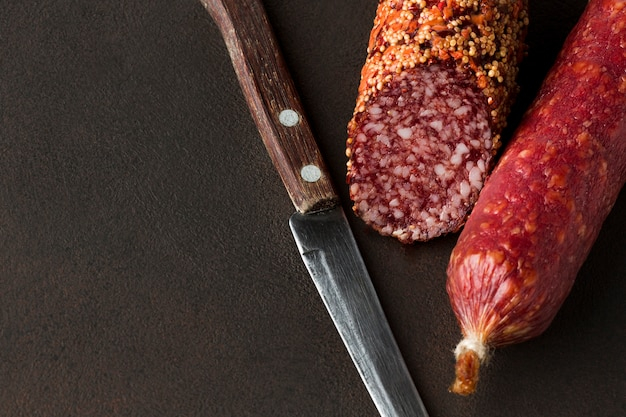 Close-up salami with knife on the table Free Photo