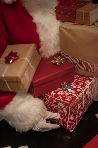 Close-up santa claus holding gift boxes Free Photo