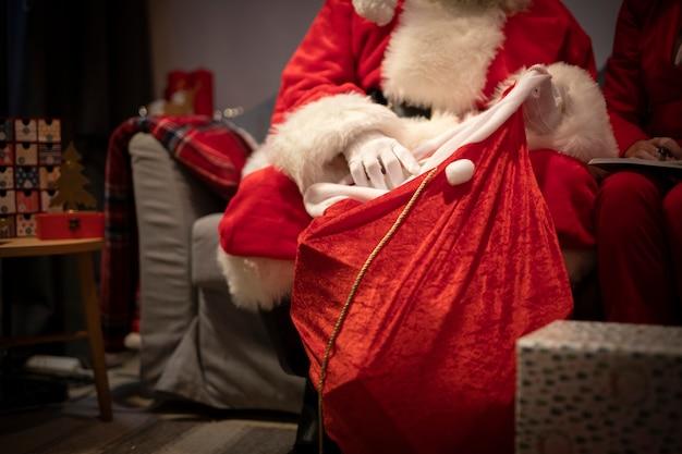 Close-up santa claus setting up presents Free Photo