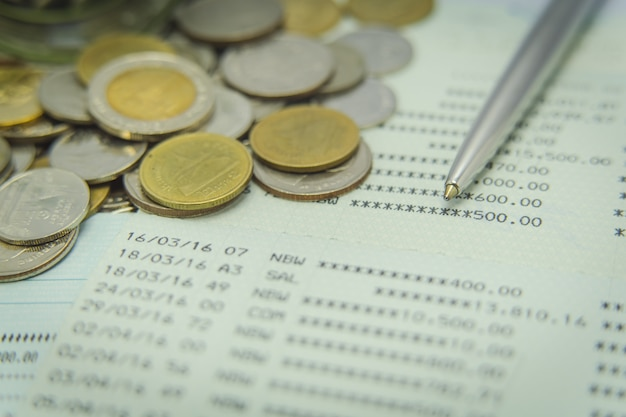 Close up of savings account passbook with a pen and coins Premium Photo