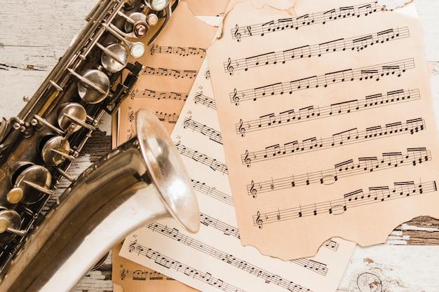 Close-up saxophone on sheet music Free Photo