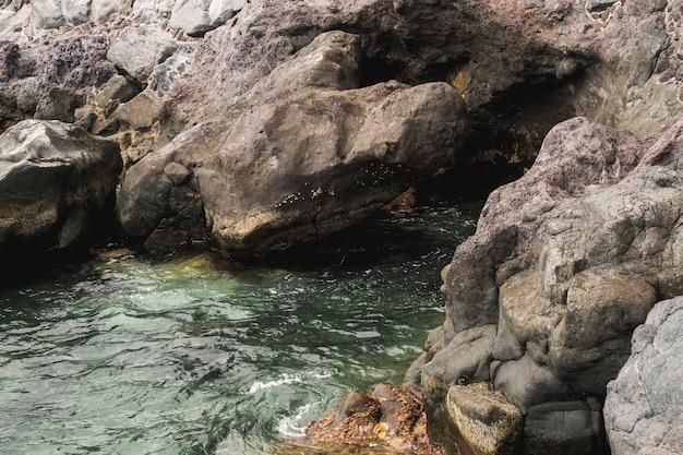 Close-up sea touching rocky shore Free Photo