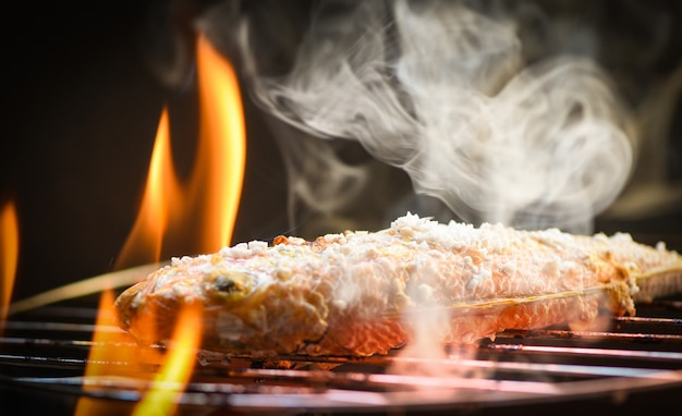 Close up of seafood grilled fish food with salt on the grill fire and smoke Premium Photo