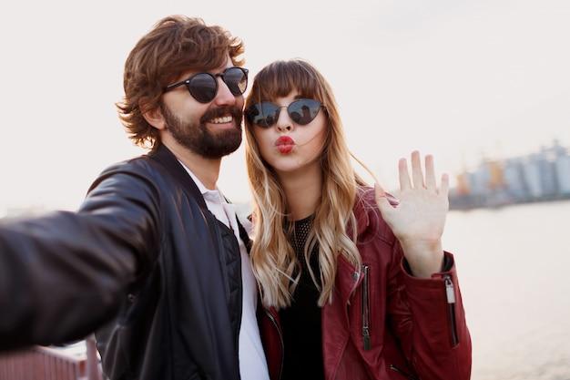 Закройте автопортрет милой игривой пары, весело проводящей романтические моменты вместе. в стильной кожаной куртке и солнечных очках. Бесплатные Фотографии