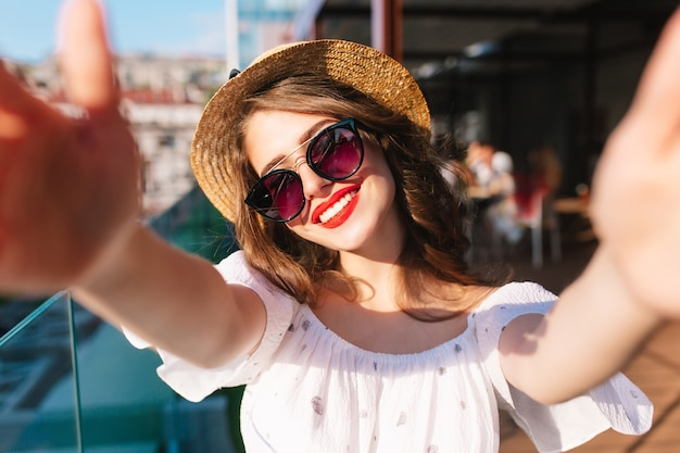 Close-up selfie-portrait of pretty girl with long hair standing on sunlight on terrace. she wears white dress, hat, red lipstick, sunglasses. she is smiling sinceriously. Free Photo