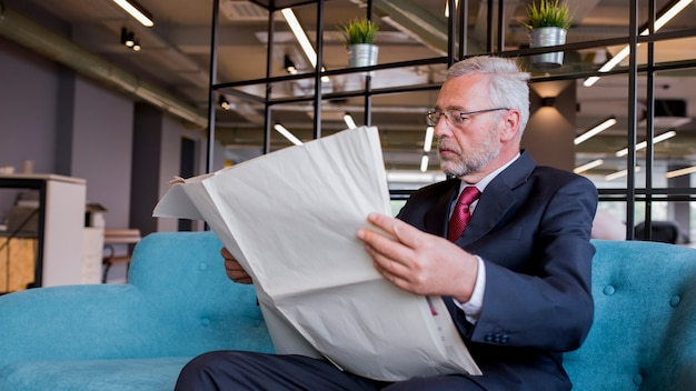 Close-up of senior businessman sitting on sofa reading newspaper in the office Free Photo