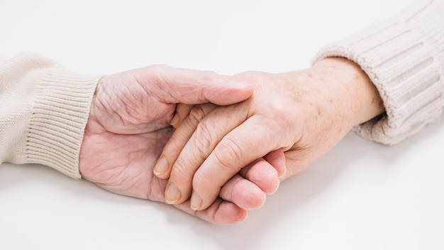 Close up of senior couple holding hands Free Photo