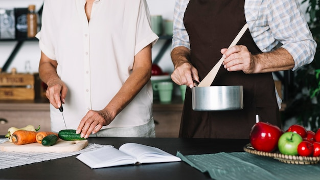 Close-up of senior couple preparing food in the kitchen Free Photo