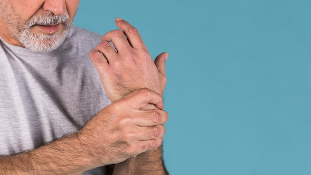 Close-up of a senior man holding her painful wrist Free Photo