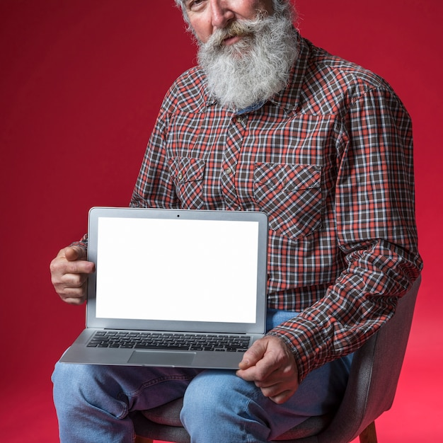Close-up of senior man showing digital tablet with blank white screen display against red backdrop Free Photo
