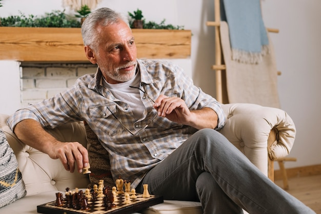Close-up of senior man sitting on sofa playing chess Free Photo