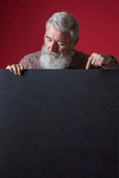 Close-up of senior man with grey beard pointing her finger on blank black placard Free Photo