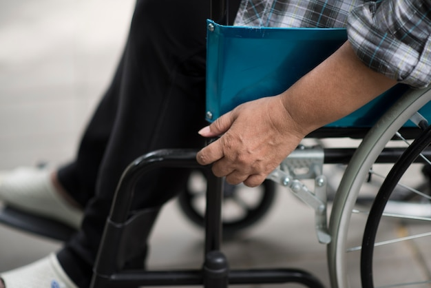 Close-up of senior woman hand on wheel of wheelchair during walk in hospital Free Photo