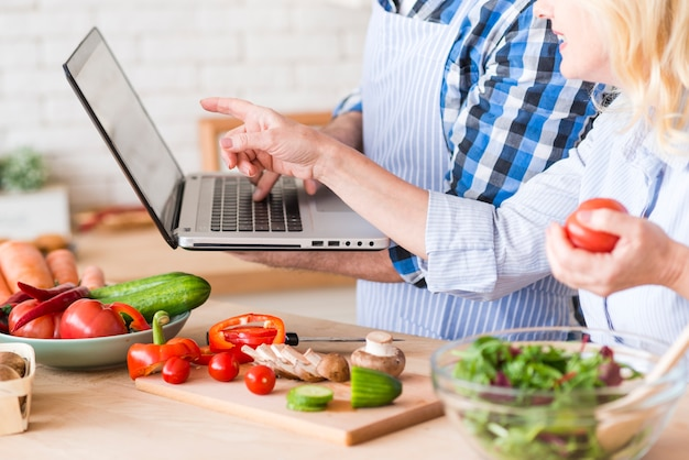 Close-up of senior woman pointing at laptop hold by her husband while preparing the vegetable salad Free Photo
