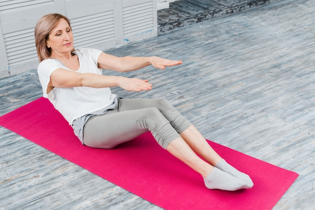 Close-up of senior woman stretching to touch toes while sitting on yoga mat Free Photo