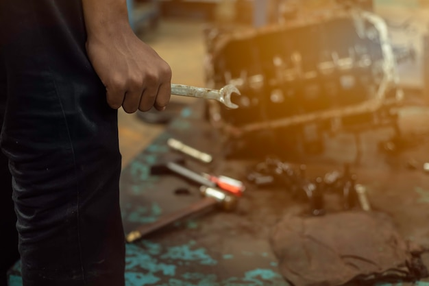 Close up, service car is people are repair a car use hand a wrench and a screwdriver to work.engine repair technicians are hold the wrench in order to repair the car. Premium Photo